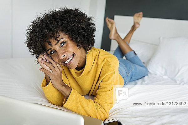Portrait of happy woman lying on bed with laptop