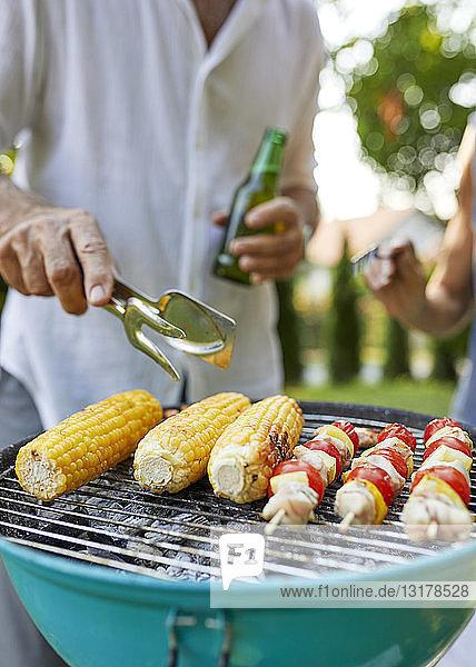 Maiskolben und Fleischspieß auf dem Grill beim Barbecue im Garten