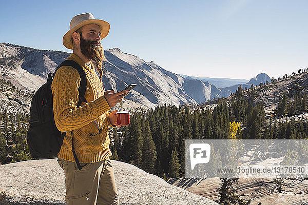 USA  Kalifornien  Yosemite National Park  Wanderer mit Smartphone und Haltebecher