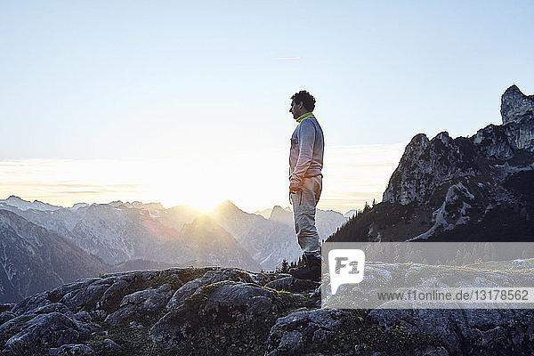 Österreich  Tirol  Rofangebirge  Wanderer bei Sonnenuntergang auf Felsen stehend