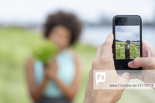 Handy-Bild einer Frau  die eine Pflanze im Freien hält