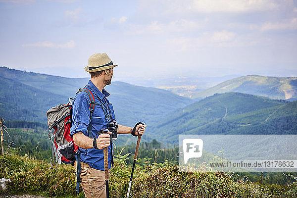 Mann bewundert die Aussicht auf die Berge während einer Wanderung