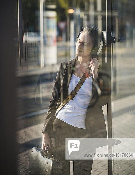Entspannte junge Frau  die in der Straßenbahnhaltestelle mit Kopfhörern Musik hört