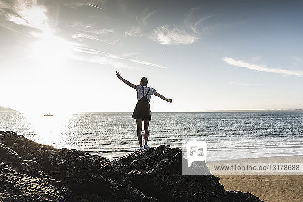 Frankreich,  Bretagne,  Rückansicht einer jungen Frau,  die bei Sonnenuntergang auf einem Felsen am Strand steht