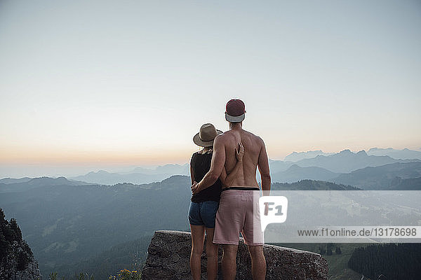 Switzerland  Grosser Mythen  young couple on a hiking trip at sunrise looking at view