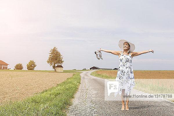 Reife Frau steht im Sommer mit ausgestreckten Armen auf abgelegenem Feldweg