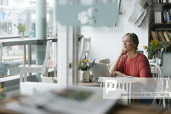 Young woman using laptop at table in a cafe