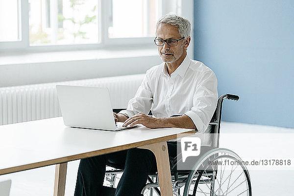 Behinderter Manager im Rollstuhl  der im Büro arbeitet