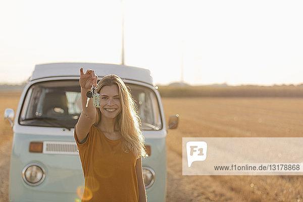 Glückliche junge Frau hält Autoschlüssel am Wohnmobil in ländlicher Landschaft
