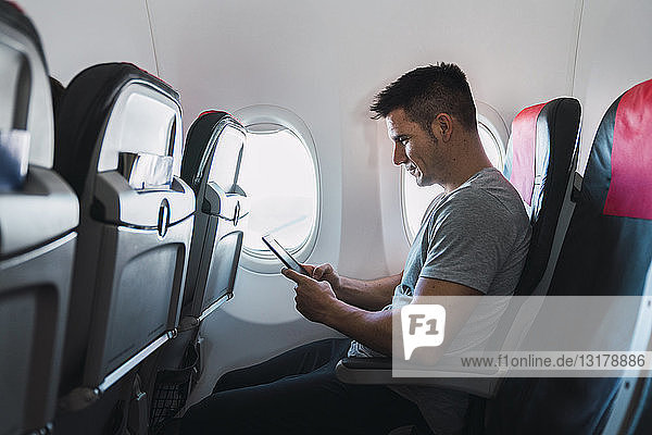 Man using ebook in airplane