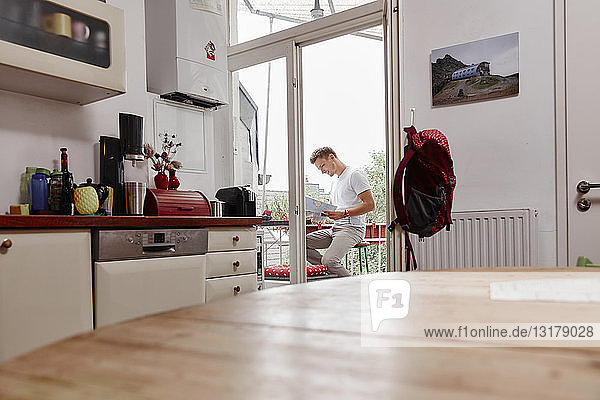 Young man sitting on balcony at home reading map