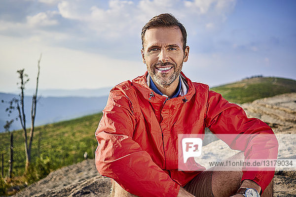 Portrait of smiling man sitting on rock during hiking trip
