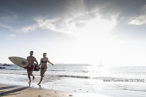 Frankreich  Bretagne  glückliches junges Paar mit einem Surfbrett  das Hand in Hand im Meer läuft