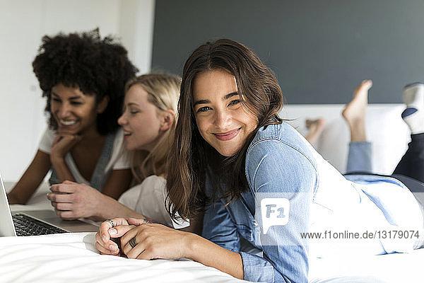 Porträt einer lächelnden jungen Frau  die mit Freundinnen am Bett liegt und einen Laptop benutzt