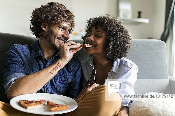 Glückliches Paar sitzt auf der Couch und isst Pizza