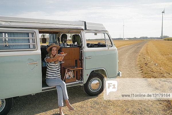 Lächelnde junge Frau hält Tasse Kaffee im Wohnmobil in ländlicher Landschaft