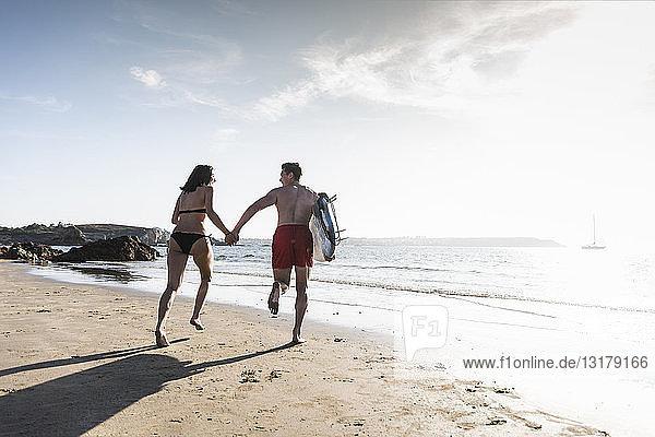 Frankreich  Bretagne  junges Paar mit einem Surfbrett  das Hand in Hand im Meer läuft