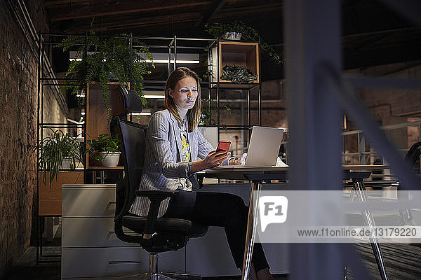 Businesswoman working in modern office  using laptop and phone