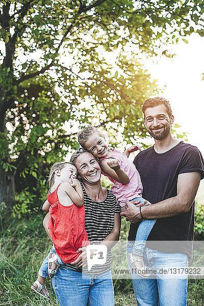 Porträt einer glücklichen Familie mit zwei in der Natur stehenden Töchtern