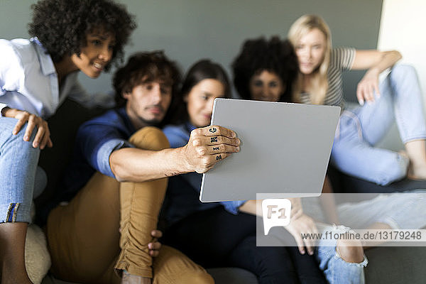 Friends sitting on couch looking at tablet