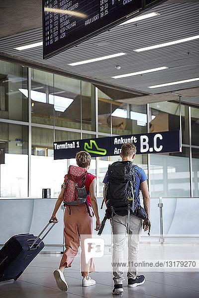 Rückansicht eines Paares zu Fuß auf dem Flughafen