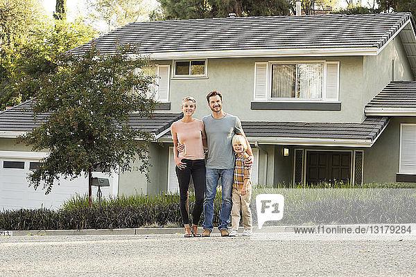 Porträt von lächelnden Eltern mit einem vor ihrem Haus stehenden Jungen