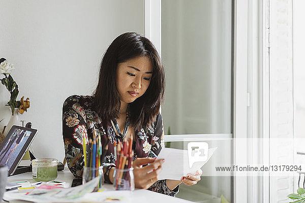 Illustratorin  die im Atelier am Schreibtisch sitzt und Zeichnungen betrachtet