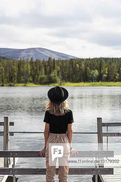 Finnland  Lappland  Frau mit Hut auf einem Steg an einem See stehend