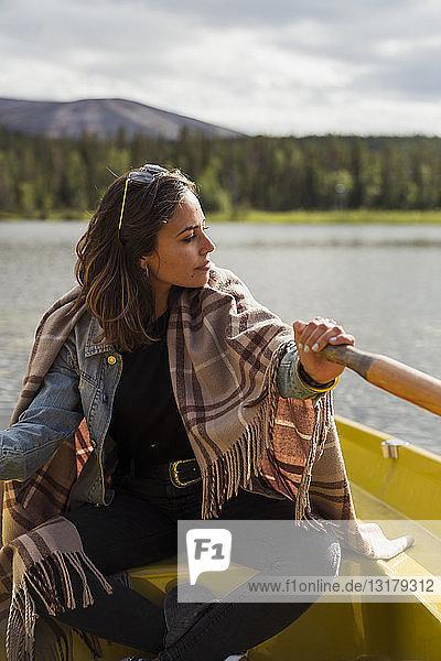 Finnland  Lappland  Frau mit einer Decke in einem Ruderboot auf einem See