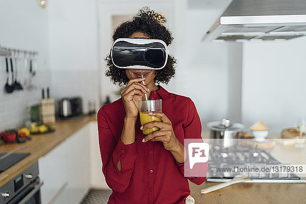Woman standing in her kitchen  wearing VR goggles  drinking orange juice