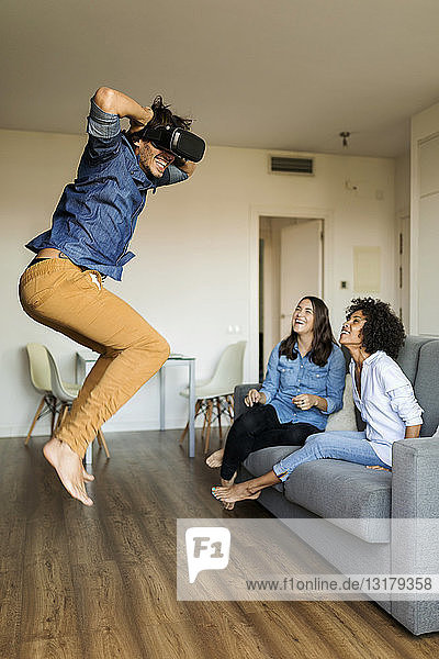 Two women watching man with VR glasses jumping at home