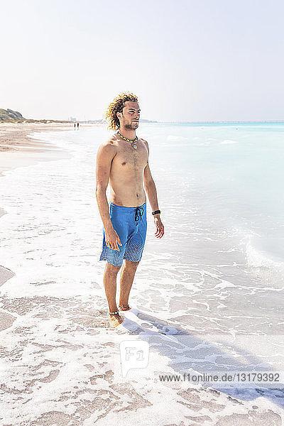 Junger Mann in Badehose steht am Meer und schaut in die Ferne