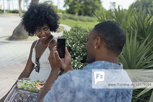 USA  Florida  Miami Beach  young man taking a picture of girlfriend eating a salad in a park