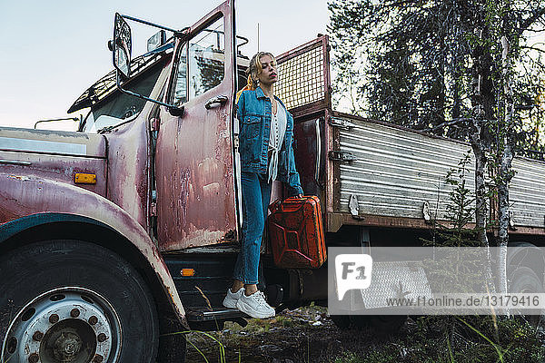 Young woman posing at a broken vintage truck  holding petrol can