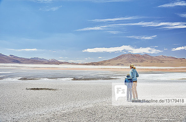 Bolivia  Laguna Colorada  mother and son at lakeshore with view to the Andes