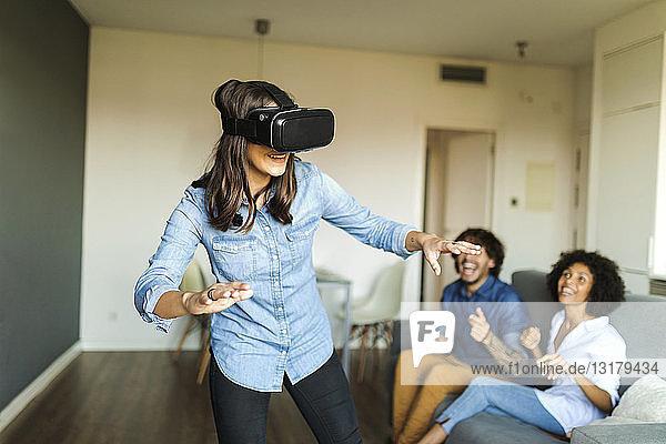 Freunde beobachten Frau mit VR-Brille zu Hause