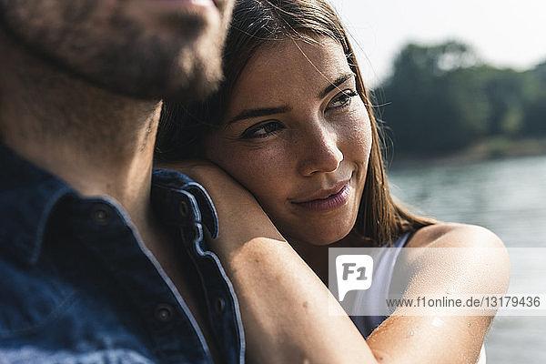 Lächelnde junge Frau  die sich am Flussufer an die Schulter eines Mannes lehnt