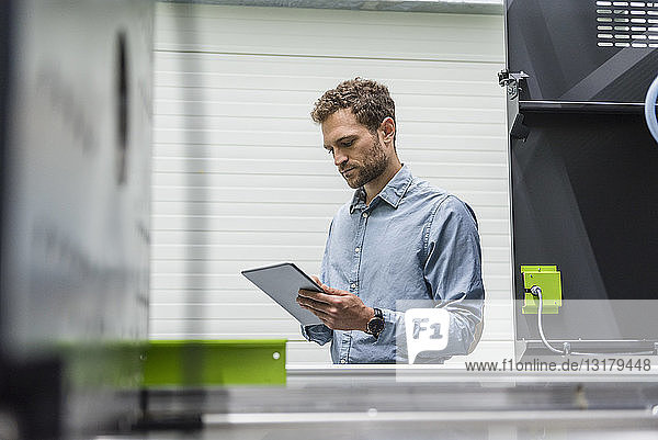 Geschäftsmann in einem High-Tech-Unternehmen  der Produktionsmaschinen mit Hilfe eines digitalen Tabletts steuert