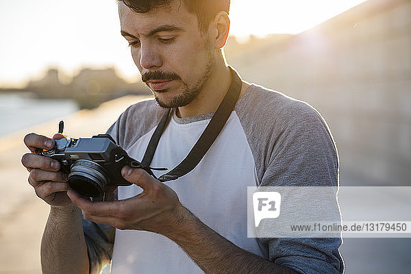 Junger Mann schaut in die Kamera auf der Uferpromenade am Flussufer