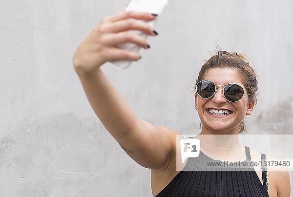 Porträt einer lachenden jungen Frau mit Sonnenbrille  die mit einem Smartphone Selbstgespräche führt