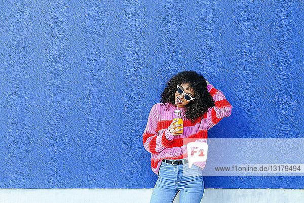 Porträt einer lächelnden jungen Frau mit einer Flasche Orangensaft vor blauer Wand stehend