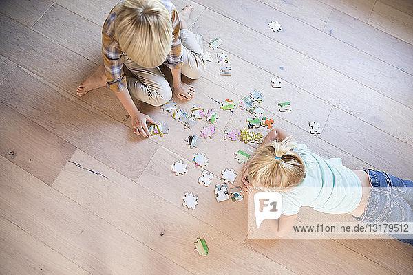 Bruder und Schwester liegen zu Hause auf dem Boden und spielen Puzzlespiele