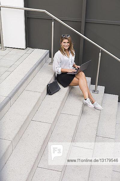 Porträt einer lächelnden Geschäftsfrau  die mit einem Laptop auf einer Treppe sitzt