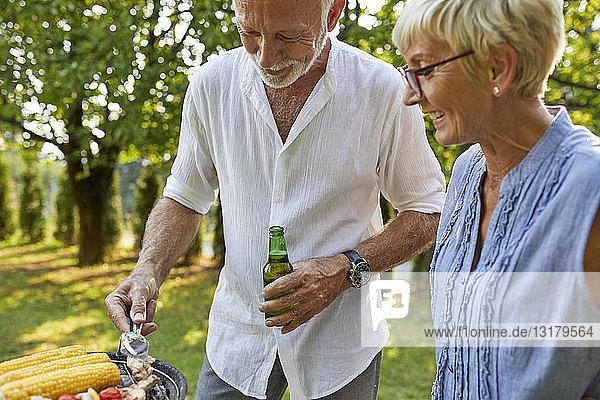 Senior couple having a barbecue in garden