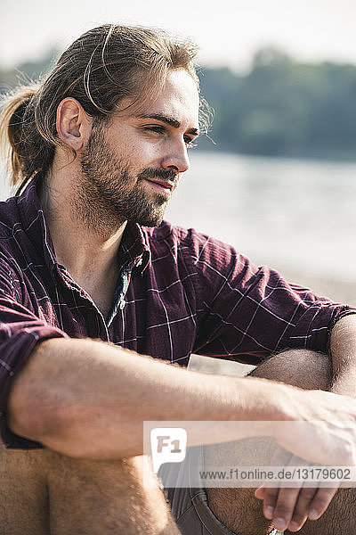 Selbstbewusster junger Mann sitzt am Flussufer