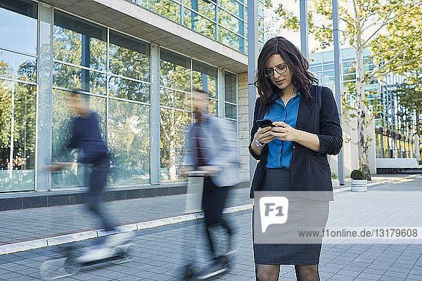Geschäftsfrau benutzt Mobiltelefon mit Roller fahrenden Pendlern