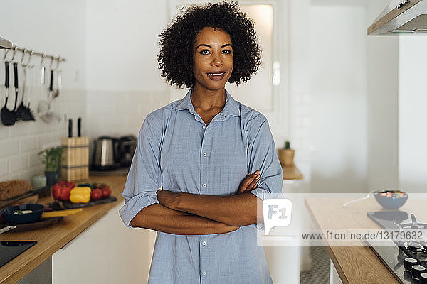 Confident woman standing in her kitchen with arms crossed