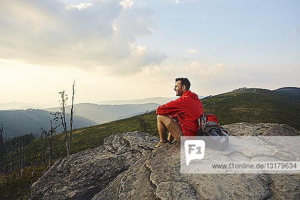 Mann sitzt auf einem Felsen und genießt die Aussicht während einer Wanderung