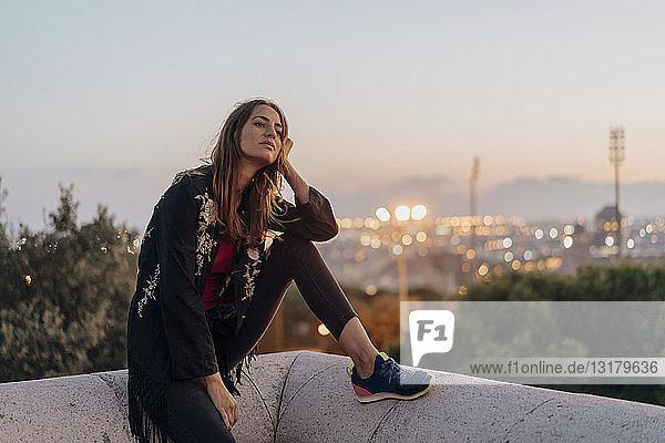 Spanien  Barcelona  Montjuic  junge Frau sitzt in der Abenddämmerung auf einer Mauer mit Stadtlichtern im Hintergrund