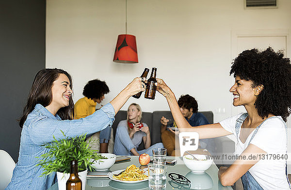 Smiling friends clinking beer bottles at dining table